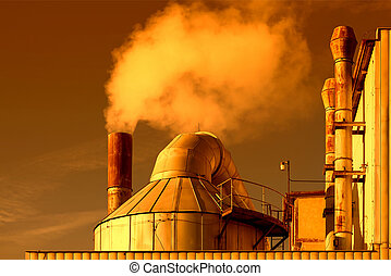 Smoking chimneys of a factory in the sunset