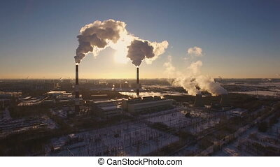 Smoking chimneys power station on sunset background in the winter. Aerial view