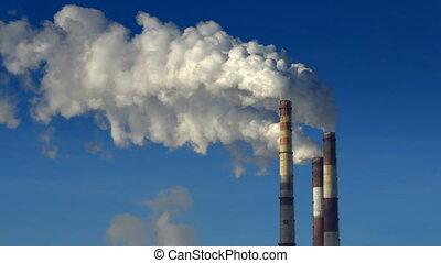 Smoking chimneys - Three smoking chimneys with blue sky