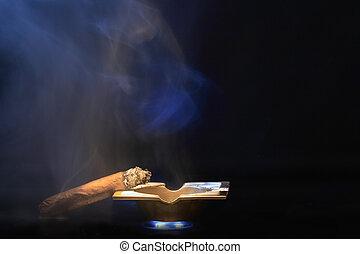 Smoking Cigar - Cuban cigar lying on bronze ash-tray on dark...