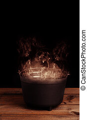 smoking halloween cauldron on wood table with black background