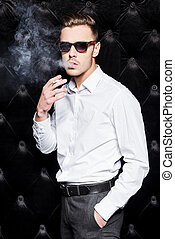Smoking handsome. Handsome young man in white shirt smoking cigarette and looking at camera while standing against black background