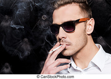 Smoking handsome. Handsome young man in white shirt smoking cigarette while standing against black background