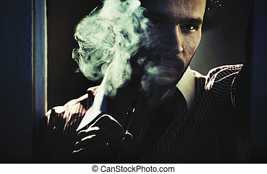 Smoking handsome man with serious look