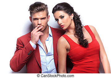 smoking hot fashion couple looking at the camera, man...