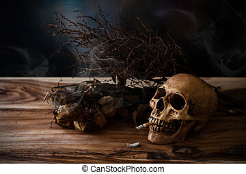 Smoking human skull with cigarette on wooden table