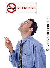 Smoking man - Man smoking cigarette under a NO SMOKING plate
