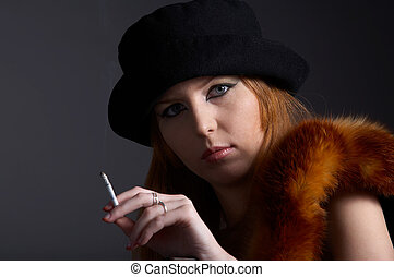 portrait of beautiful redhead pale skinned model in fur fox scarf and black hat with cigarette