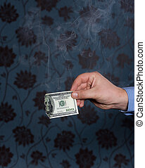 Smoking one hundred dollars bill in hand