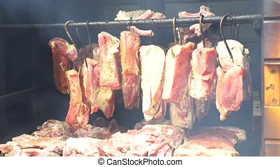Smoking pork meat, bacon and sausages, food preparation...