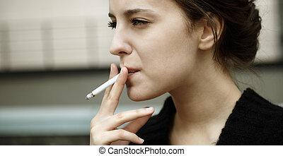 smoking - real young woman smokes on the street, selective ...