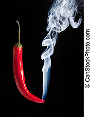 Smoking red hot chilli pepper with burning tip and smoke
