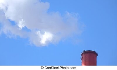 Smoking red smoke stack against sunny blue sky. 4K telephoto...