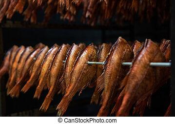 Smoking sea bass fish in smokehouse box