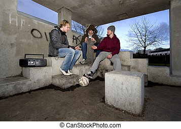 Smoking shelter - Three adolescent youths lighing cigarettes...