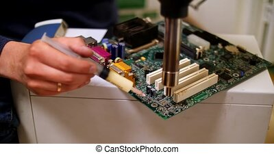 smoking soldering iron on a computer motherboard closeup - ...