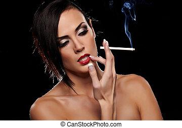 Smoking - Elegant brunette woman smoking a cigarette on...