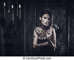 Smoking tattooed beautiful woman  in old spooky interior