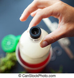 Smoking weed through the bottle. Cannabis use through homemade bong close-up