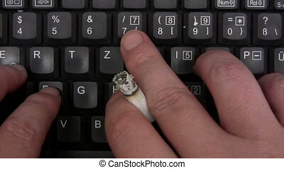 Smoking While Typing - Male hands holding a cigarette white...