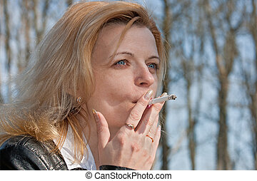 smoking woman - pretty girl smoking in the park in sunny day