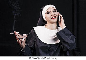 Smoking young nun. Studio shoot on black backround