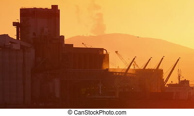Smoky Industrial Facility At Sunset - Industrial facility...