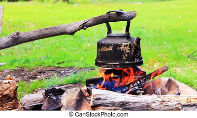 Smoky tourist kettle on fire in camping picnic