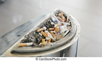 Smoking cigarettes in a dirty ashtray overflowing