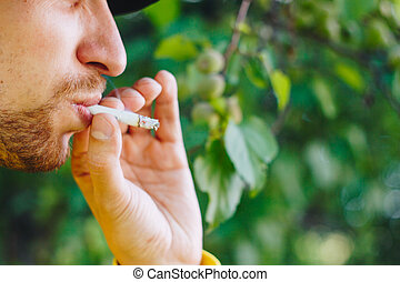 smoldering cigarette in the hand of a man with a beard on nature against the background of green trees. Nicotine tobacco smoke. Unhealthy Lifestyle. Close-up, ash. Smoking break