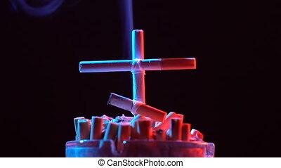 Smoldering cross of cigarettes. - Smoldering cross of...