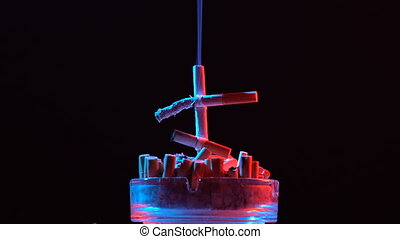 Smoldering cross of cigarettes in an ashtray