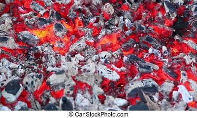 Smoldering embers with small amount of smoke and fire