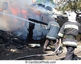 Smoldering remains of a ghetto house with a fireman spraying water firefighters extinguish a fire in an apartment house