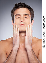 Smooth and healthy skin. Handsome young shirtless man touching his face with hands and keeping eyes closed while standing against grey background