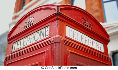 Smooth backward 4k shot of the Top of a London telephone booth with a blurry brick building as background