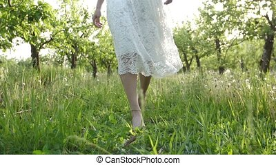 Smooth barefoot female legs walking on juicy grass -...
