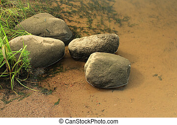 Smooth boulders lies in the water on  river bank