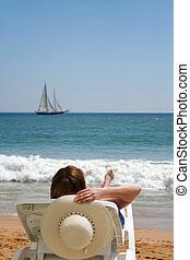 smooth sailing - sailboat crosses the horizon while a woman...