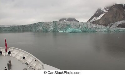 Smooth water surface on background of snow mountains of Arctic view from ship.