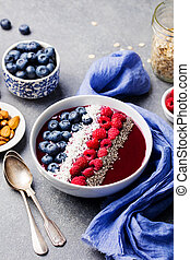 Smoothie bowl with fresh raspberry, blueberry, coconut flakes and chia seeds. Grey stone background.