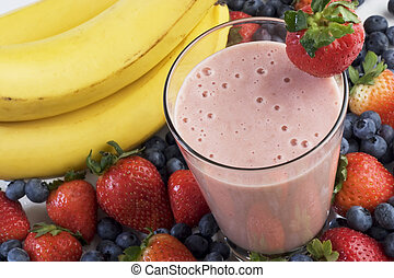 Smoothie surrounded by bananas, strawberries, and blueberries.