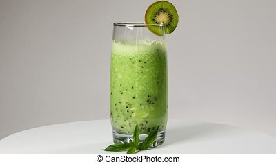 Smoothies of kiwi with a slice of kiwi rotating on a turntable