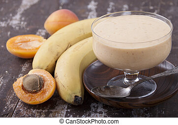 Smoothies with apricot and banana in a vase on an old wooden table
