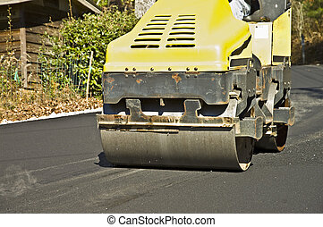 A machine smoothing the new asphalt on a road.