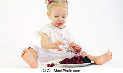Smudged baby girl eats berries against white background -...