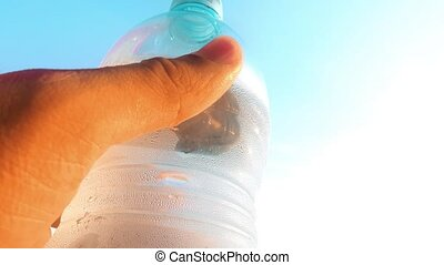 Smudging dew on cold bottle of water on a hot summer day -...