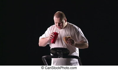 Snack at the Gym - Man eating and drinking on the treadmill...