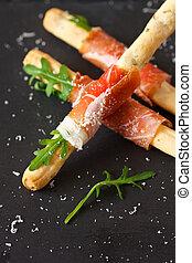 Snack. - Bread sticks grissini with prosciutto ham and...