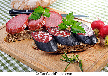 Tyrolean rye bread with smoked sausages, decorated by red radish, parsley and rosemary